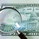 Magnifying glass being used to investigate fake money