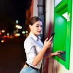 Young woman using an ATM at night
